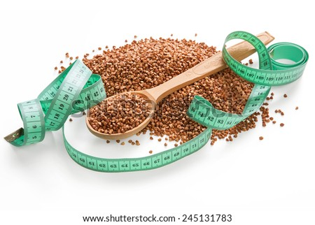 Pile of buckwheat groats / premium buckwheat groats on white background with wooden spoon and measuring tape  - stock photo