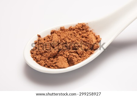 Pile of cacao powder in white ceramic spoon on white background - stock photo