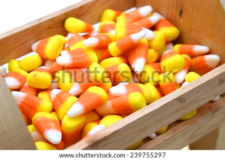 pile of candy corn for Halloween in wooden crate, isolated on white background  - stock photo