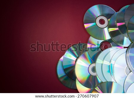 Pile of CDs on red background - stock photo