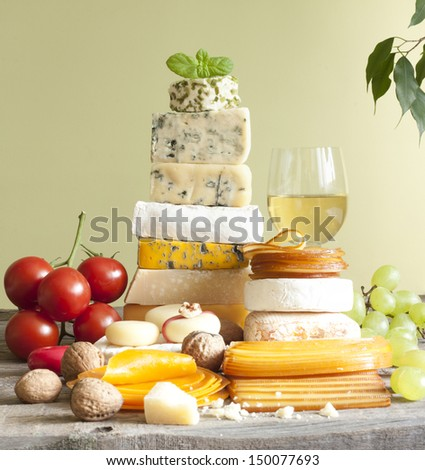 Pile of cheese many various types with wine grapes and walnuts - stock photo