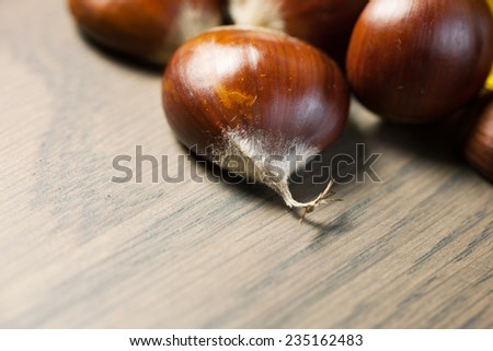 Pile of chestnuts on a wooden table - stock photo