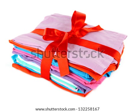 Pile of clothing with red ribbon and bow isolated on white - stock photo