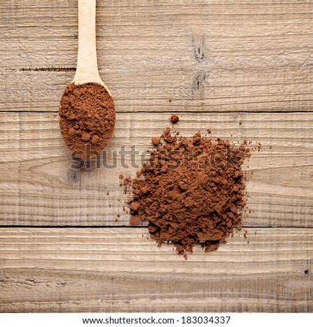 Pile of cocoa powder on wooden background - stock photo