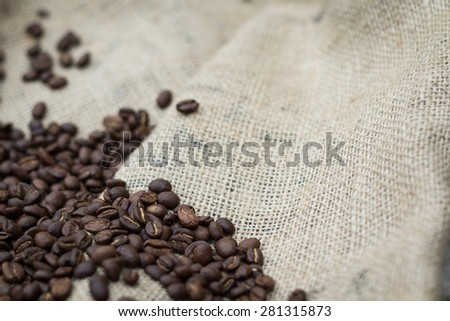 Pile of coffee beans on burlap sack - stock photo
