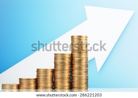 Pile of coins and growing arrow. Earning and saving more money. Pile of 500 yen coins with upside growing arrow. Blue reflection background.  - stock photo
