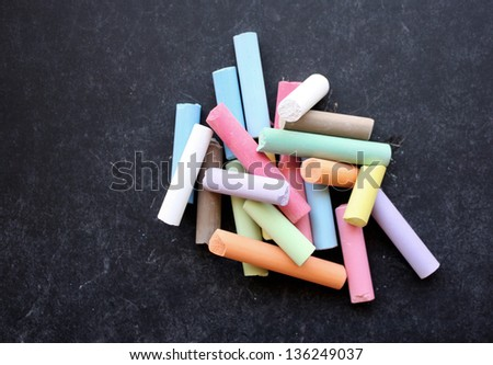 Pile of colored chalk on blackboard - stock photo