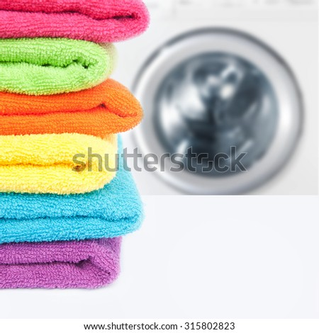 Pile of colorful clean towels with washing machine  - stock photo