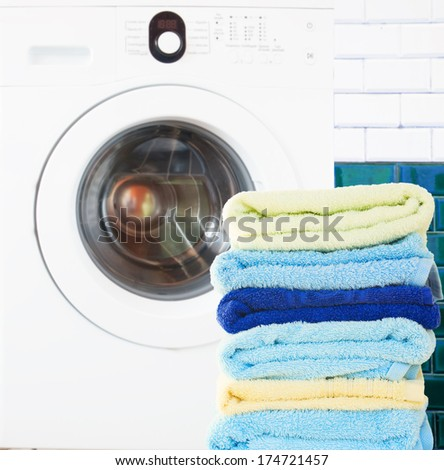 pile of colorful  clean towels with washing machine in bathroom - stock photo