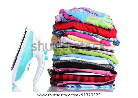 Pile of colorful clothes and electric iron isolated on white - stock photo