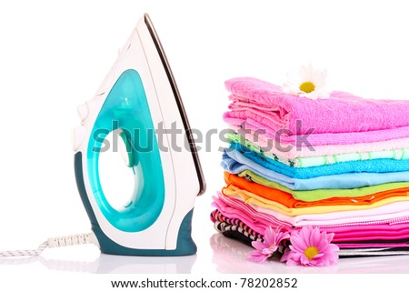 Pile of colorful clothes and electric iron  over white background - stock photo