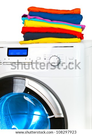 Pile of colorful clothes on the washing machine - stock photo
