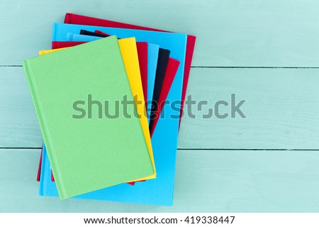 Pile of colorful hardcover books stacked on a green stained wooden table with a green book on the top with copy space, overhead closeup view - stock photo