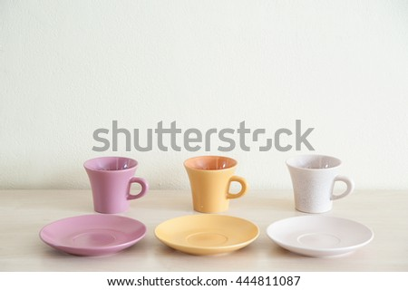 Pile of colorful modern coffee cups on wooden table with dishes for prepare serve. - stock photo