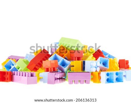Pile of colorful plastic toy construction bricks isolated over the white as a copyspace background compostion - stock photo