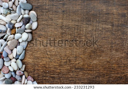 pile of colorful stones with waveform on background wood texture - stock photo