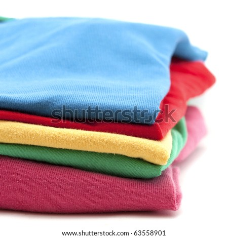 pile of colorful T-shirts isolated on white - stock photo