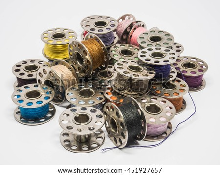 Pile of colorful thread spools for sewing machine - stock photo