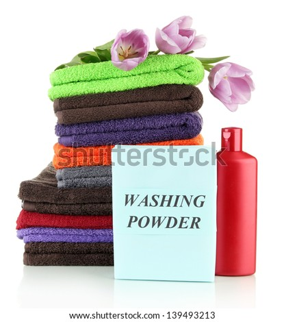 Pile of colorful towels, wash powder and bottle of conditioner for laundry, isolated on white - stock photo