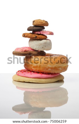 pile of cookies and donuts cutout on white background - stock photo