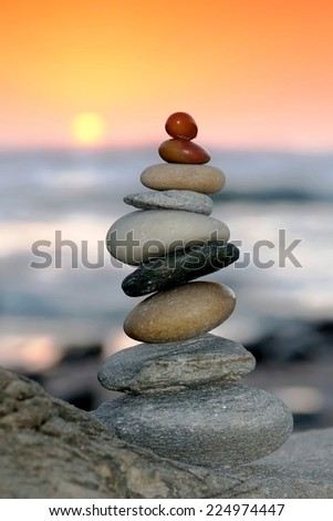 Pile of delicately balanced stones with the ocean and sunset in the background - stock photo