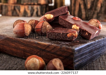 Pile of delicious chocolate bars with whole nuts on wood, Warm composition of chocolate pieces with hazelnuts - stock photo