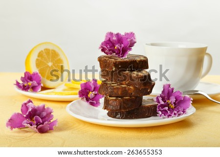 Pile of delicious chocolate cake slices with the cookies filling, decorated violet flowers on a white plate with lemon and cup of tea. - stock photo