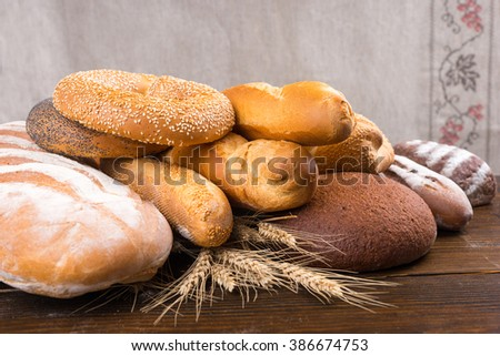 Pile of different types of baked bread loaves, baguettes, bagels and rolls on top of whole wheat stalks over wood table - stock photo