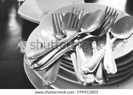 pile of dirty dishes in black and white - stock photo