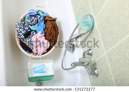 Pile of dirty laundry in bath washing machine green bathroom - stock photo