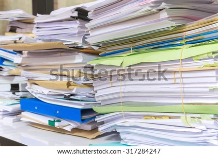 Pile of documents on desk stack up high waiting to be managed. - stock photo