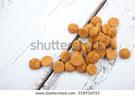 Pile of Dutch candy pepernoot on white wooden background - stock photo