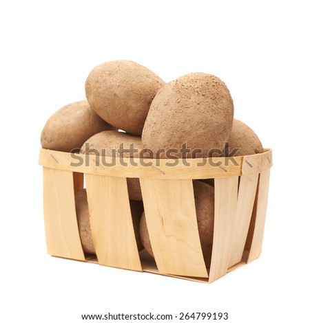 Pile of earth dirty potatoes in a wooden basket, composition isolated over the white background - stock photo