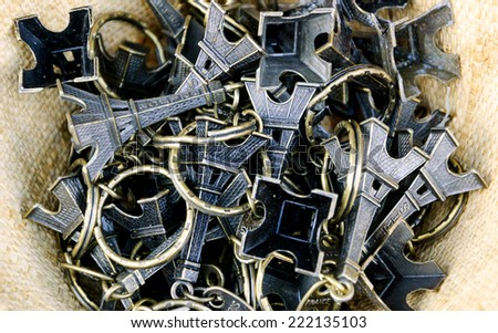 Pile of Eiffel Tower trinkets in the wicker basket. Typical souvenir from Paris. - stock photo