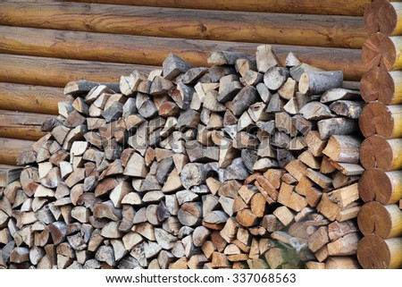 pile of firewood near wooden house - stock photo
