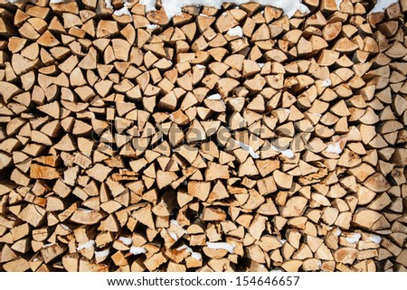 pile of firewood. snowy firewoods in winter forest - stock photo