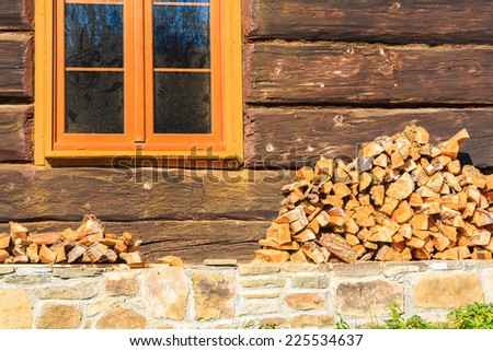 Pile of firewood stacked up in front of a house in Beskid Niski Mountains, Poland - stock photo