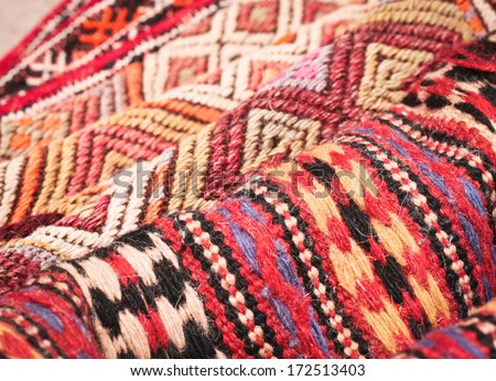 Pile of folded kilim rugs with shallow depth of field - stock photo