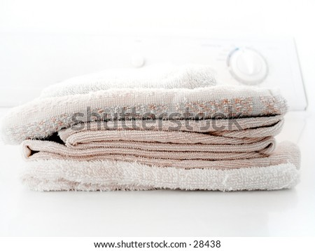 Pile of folded towels on a clothes dryer. - stock photo
