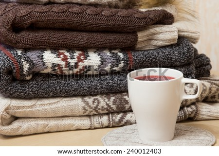 Pile of folded winter sweaters and white cup of hot wine - stock photo