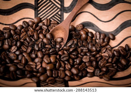 pile of fresh and bio aromatic coffee beans in african bowl and wooden spoon - stock photo