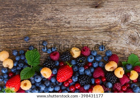 pile  of fresh  berries mix on wood, top view - stock photo