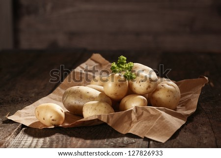 Pile of fresh healthy whole raw potatoes on a sheet of crumpled brown paper with copyspace - stock photo