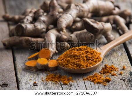 pile of fresh turmeric roots on wooden table - stock photo