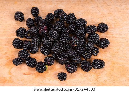 Pile of freshly picked ripe juicy autumn blackberries on a wooden board ready for dessert, high angle view - stock photo