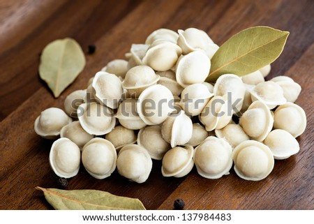 Pile of frozen mini pelmeni on a wooden board, selective focus - stock photo