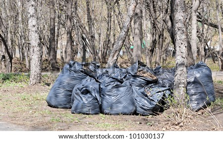 Pile of full black garbage bags with tall city buildings in the background - stock photo