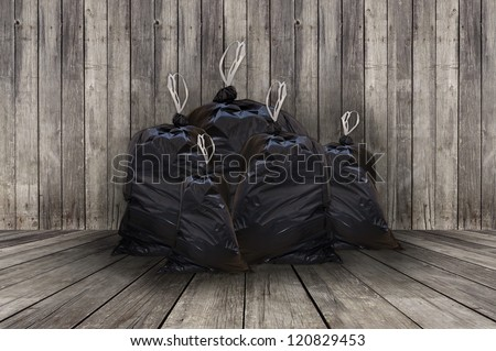 Pile of full black garbage bags with wooden background - stock photo
