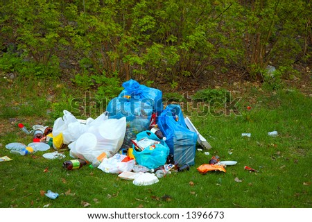 Pile of garbage on green grass in the nature environment problems - stock photo