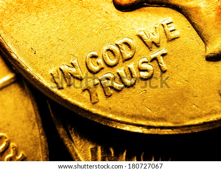 Pile of gold coins and bullion with dark background and words In God We Trust - stock photo